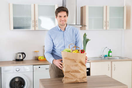 paper bag: Happy Young Man Standing With Grocery Bag In Kitchen Room