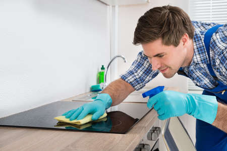 Young Happy Male Janitor Cleaning Induction Stove In Kitchen 写真素材