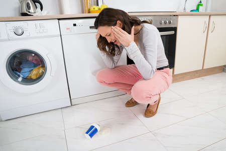 destroying: Frustrated Young Woman Looking At Yoghurt Fallen On The Floor In Kitchen Room