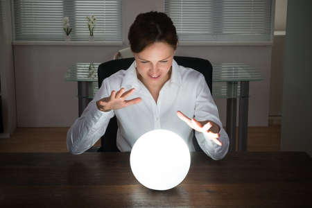 soothsayer: Empresaria joven que mira en el futuro en una bola de cristal en la oficina Foto de archivo