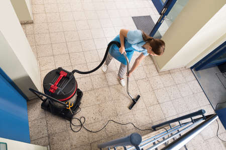 High Angle View Of Young Female Janitor Vacuuming Floor Stockfoto