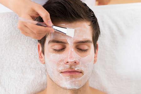 antifaz: Las manos del terapeuta con cepillo Aplicar la mascarilla a un hombre joven en un spa