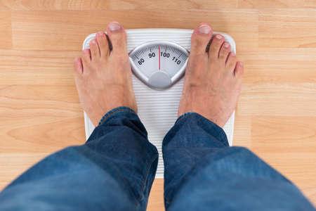 sobrepeso: Parte inferior del hombre de pie en báscula de pesaje