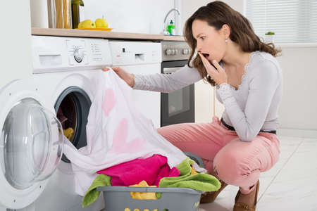 stain: Shock Young Woman Looking At Stained Cloth In Kitchen