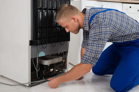 freezer: Young Male Repairman Making Refrigerator Appliance In Kitchen Room