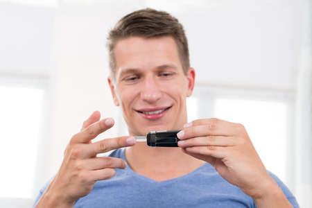 azucar: Primer De La Mujer Feliz Hombre que controla el nivel de az�car de sangre con gluc�metro Foto de archivo