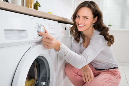 laundry room: Close-up Of Young Woman Pressing Button Of Washing Machine In Kitchen Stock Photo