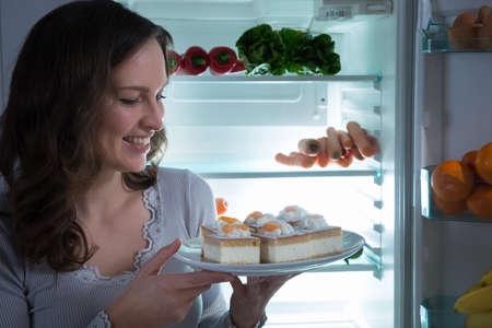 woman eating cake: Young Happy Beautiful Woman Eating Cake Near The Open Fridge