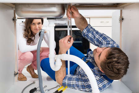Young Worker Fixing Sink In Front Of Woman Crouching On Floor In Kitchen
