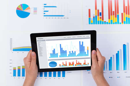 analyzing: Close-up Of Person Analyzing Financial Graph Diagram On Digital Tablet Stock Photo