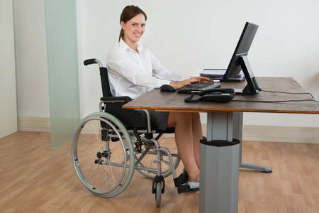 wheelchair access: Happy Businesswoman Sitting On Wheelchair While Working On Computer At Desk