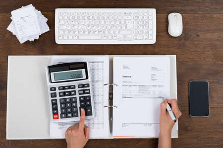 High Angle View Of Person Hands Calculating Invoice With Calculator