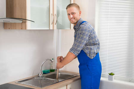 stoppage: Young Happy Plumber Using Plunger In Kitchen Sink