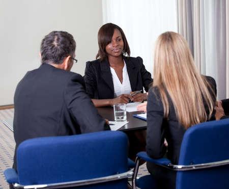 job: Grupo de los gestores de entrevistar candidata mujer joven y bonita de trabajo en la oficina