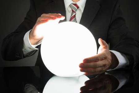 adivino: Primer plano del hombre de negocios Predicción de futuro con la bola de cristal en el escritorio