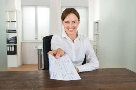 chequera: Feliz empresaria sentado en el escritorio de oficina ofrecimiento Cheque En Foto de archivo