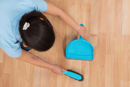 brooming: Young Woman Brooming Wooden Floor With Broom And Dustpan
