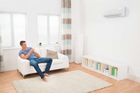 heat home: Young Man On Sofa Operating Air Conditioner With Remote Control Stock Photo