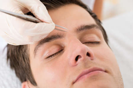 beautician: Close-up Of Beautician Hands Plucking Handsome Man Eyebrows With Tweezers Stock Photo