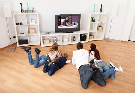 familj: Unga familjen tittar på TV tillsammans hemma Stockfoto