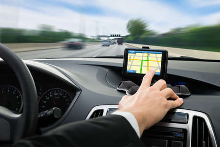 Close-up Of A Person's Hand Using Gps Navigation System In Car 写真素材