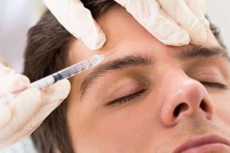 美容クリニックでボトックス治療を受ける若い男
