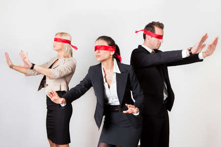 Group of disoriented businesspeople with red ribbons on eyes Stock Photo