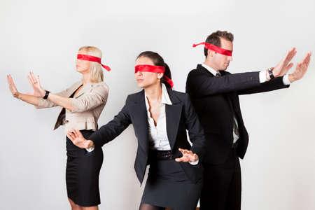 confundido: Grupo de empresarios desorientados con cintas rojas en los ojos Foto de archivo