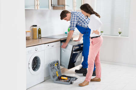 overall: Young Woman Looking At Male Worker In Overall Repairing Oven In Kitchen Stock Photo
