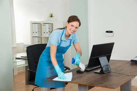 routine: Young Happy Female Janitor Cleaning Wooden Desk With Rag In Office