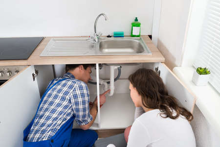 service man: Plumber Showing Damage In Sink Pipe To Woman Plumber At Home