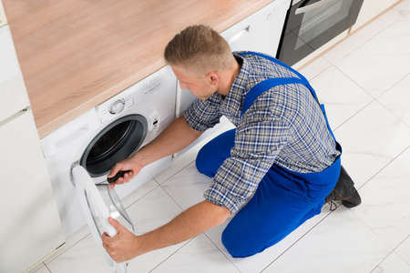 angle: High Angle View Of Male Worker In Overall Fixing Washer With Screwdriver