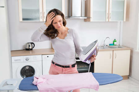Hot house: Young Woman With Electric Iron And Cloth In Kitchen Stock Photo