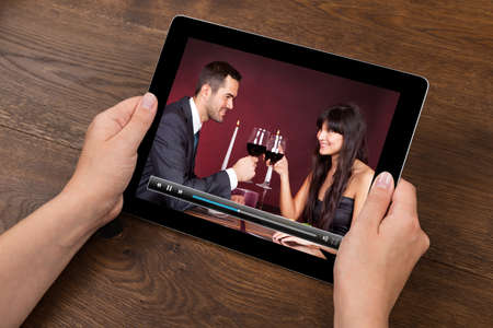 viewing: Close-up Of Person Hands With Digital Tablet Showing Video At Desk Stock Photo