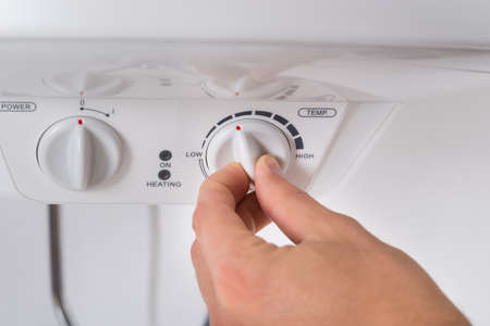 Close-up Of Person Hands Turning The Knob Of Electric Boiler