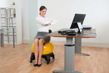 pilate: Young Happy Businesswoman Exercising On Pilates Ball In Office