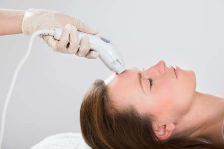 beauty center: Young Woman Receiving Laser Hair Removal Treatment At Beauty Center Stock Photo