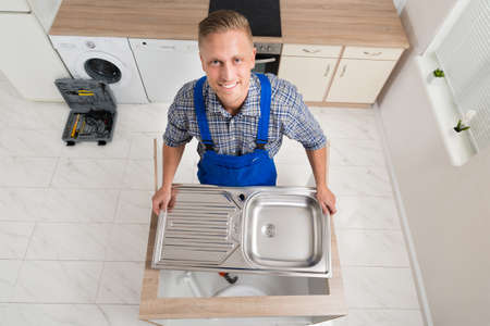 stainless steel sink: High Angle View Of Male Plumber Fixing Stainless Steel Sink