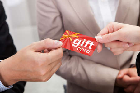Close-up Van Businessperson handen geven Gift Card Om Andere Businessperson Stockfoto
