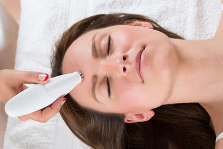 hair removal: Young Woman Receiving Microdermabrasion Therapy In Beauty Clinic