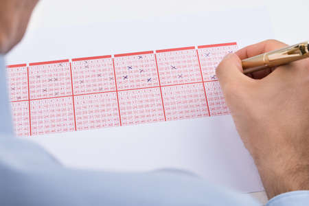lottery win: Close-up Of Businessperson Marking On Lottery Ticket Stock Photo