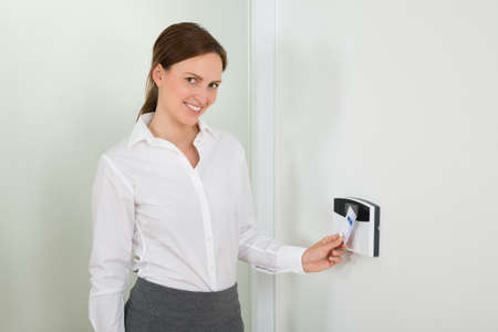 keycard: Young Businesswoman Smiling While Inserting Keycard In Door Security System
