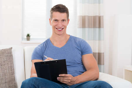 hombre escribiendo: Happy Young Man Writing On Clipboard While Sitting On Sofa