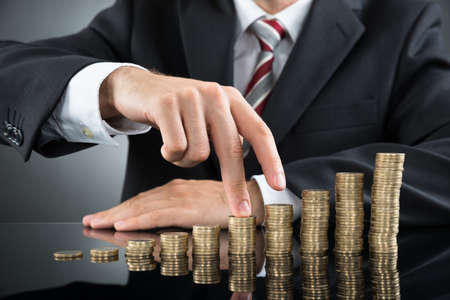 Close-up Of Businessman's Fingers Walking On Pile Of Coins At Desk