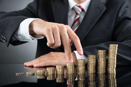 Close-up des doigts d'affaires Marcher sur pile de pièces Au bureau Banque d'images