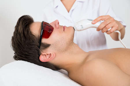 beauty center: Young Man Receiving Laser Hair Removal Treatment At Beauty Center Stock Photo
