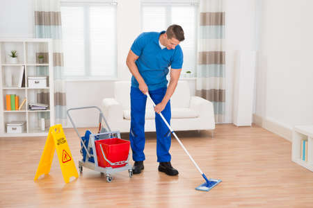 mop: Happy Worker With Cleaning Equipments And Wet Floor Sign In House