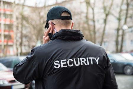 seguridad en el trabajo: Guardia de seguridad En Uniforme Negro Escucha Con Auricular Foto de archivo