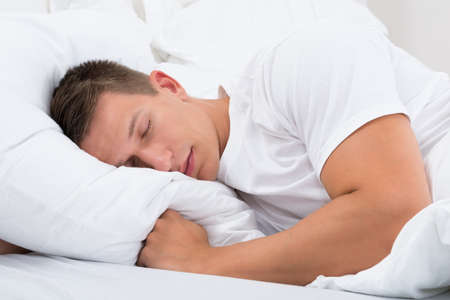 dormir: Hombre joven que duerme en cama en dormitorio Foto de archivo