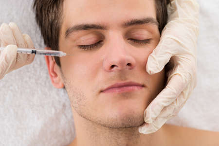 Close-up Of Man Receiving Wrinkle Treatment On Face In Beauty Clinic